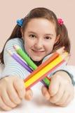 Χαμογελώντας μολύβια χρώματος εκμετάλλευσης κοριτσιών Στοκ φωτογραφία με δικαίωμα ελεύθερης χρήσης