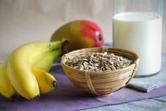 用早餐用滚的燕麦粥、香蕉、芒果和牛奶 免版税库存照片