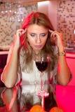 哀伤的妇女在有杯的厨房里酒 免版税图库摄影