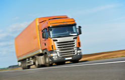 在蓝天的橙色卡车拖车 免版税库存图片