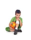 Мальчик с поврежденным шариком ноги и футбола Стоковые Фото