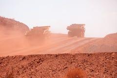 运转在铁矿山的开采的卡车 免版税库存图片
