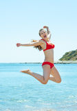跳在海边的愉快的少妇 免版税库存照片