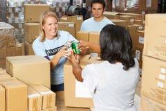 Волонтеры собирая пожертвования еды в пакгаузе Стоковое Изображение RF