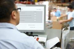 计算机终端的人员在配给物仓库里 免版税图库摄影