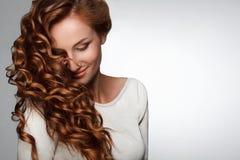 红色头发。 有美丽的卷发的妇女 库存图片