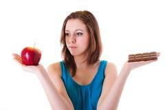 健康苹果或不健康的巧克力? 免版税图库摄影