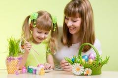 母亲和儿童女孩油漆复活节彩蛋 库存照片