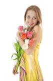 有春天郁金香花束的愉快的微笑的女孩。 免版税库存图片