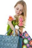 有春天郁金香和购物的礼品袋子花束的愉快的微笑的女孩。 免版税库存图片