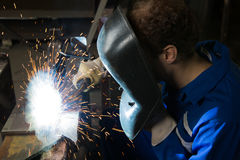 人创建许多火花的焊接钢 库存照片