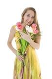 一个愉快的女孩的纵向有春天郁金香花束的。 库存图片