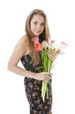 一个愉快的女孩的纵向有春天郁金香花束的。 库存照片