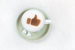 与恶赞许的热奶咖啡 免版税库存照片