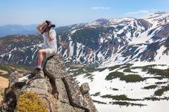 摄影师做在山的照片 库存图片