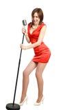 一件红色礼服的可爱的女孩唱歌到话筒的 免版税图库摄影