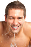 年轻在他的表面的人喷洒的水在刮以后在卫生间里 库存照片