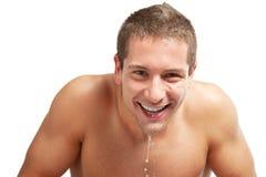 年轻在他的表面的人喷洒的水在刮以后在卫生间里 免版税图库摄影