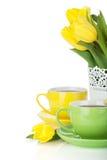 黄色郁金香和二个茶杯 免版税库存图片