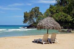 在田园诗热带沙子的海滩睡椅和伞靠岸 免版税库存图片