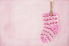 在粉红彩笔背景的女婴袜子 库存图片