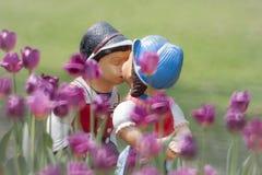 二个亲吻的玩偶在郁金香庭院里。 库存图片