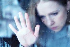 视窗的忧郁和哀伤的女孩在雨中 免版税库存照片