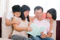 父项和儿童阅读书在家。 免版税库存照片