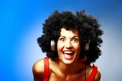 有非洲的发型穿戴耳机的愉快的妇女 免版税库存图片
