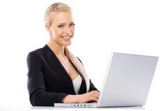 研究膝上型计算机的逗人喜爱的白肤金发的女商人 库存图片