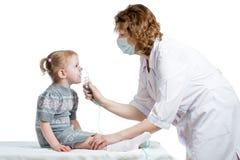 拿着孩子呼吸的医生吸入器屏蔽 免版税库存照片