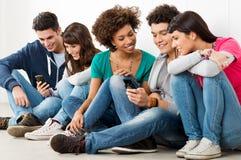 Друзья смотря сотовый телефон Стоковое Изображение RF