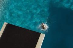 游泳者潜水的腿在水池的 免版税库存图片