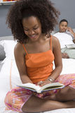 少妇读书小说在卧室 免版税库存照片