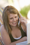 Женщина с компьтер-книжкой используя сотовый телефон Стоковое Изображение