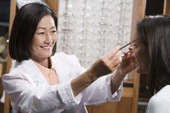 协助患者的愉快的中国验光师 免版税库存照片