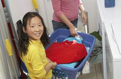 女孩帮助的母亲洗涤的衣裳 免版税库存照片