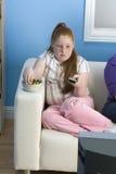 十几岁的女孩坐的观看的电视 库存图片
