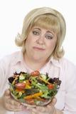 拿着碗沙拉的不快乐的妇女 免版税库存图片