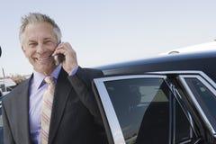 使用手机支持的汽车的商人 免版税库存照片