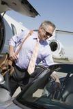 保留行李的资深商人在汽车 免版税库存照片