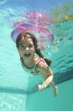 游泳的女孩在水面下 免版税库存图片