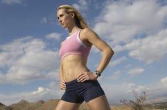 站立用在臀部的手的母慢跑者户外 免版税库存图片