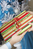 交换礼物的手由圣诞树 库存照片