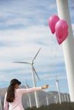 使用与气球的女孩在风力场 库存照片