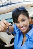 显示新的汽车钥匙的年轻女实业家 免版税库存图片