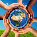 Πολυφυλετικά χέρια μαζί σε όλη την παγκόσμια υδρόγειο Στοκ εικόνα με δικαίωμα ελεύθερης χρήσης