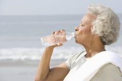 资深在海滩的妇女饮用水 图库摄影