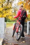 有自行车的妇女骑自行车者和背包在秋天停放 免版税库存图片