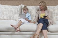 Сын женщины наблюдая используя таблетку цифров Стоковое Изображение